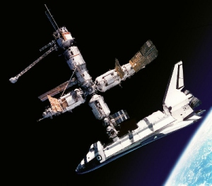 A view of the US Space Shuttle Atlantis and the Russian Space Station Mir during STS-71 as seen by the crew of Mir EO-19 in Soyuz TM-21. Cosmonauts Anatoliy Y. Solovyev and Nikolai M. Budarin, Mir-19 Commander and Flight Engineer, respectively, temporarily undocked the Soyuz spacecraft from the cluster of Mir elements to perform a brief fly-around. They took pictures while the STS-71 crew, with Mir EO-18's three crew members aboard, undocked Atlantis for the completion of this leg of the joint activities. Solovyev and Budarin had been taxied to Mir by Atlantis.