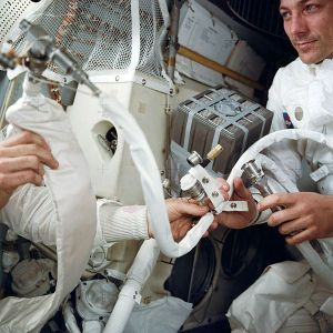 "Astronaut John Swigert on the right. An unseen Lovell on the left holds in his right hand the feed water bag from the Portable Life Support System (PLSS). It is connected to a hose (center) from the Lunar Topographic (Hycon) Camera. In the background is the ""mail box,"" a jury-rigged arrangement which the crew men built to use the CM lithium hydroxide canisters to scrub CO2 from the spacecraft's atmosphere. The ""mail box"" was designed and tested on the ground before it was suggested to the Apollo 13 astronauts."