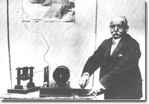 Marconi's first transmitting set constructed at Bologna (his father's home) in 1894. It consists of a morse key, a coil, and a large spark gap, one side of which was earthed, the other connected to the tin plate aerial supported above by bamboo canes. The demonstrator shown in this photo is Mr. G.S. Kemp, Marconi's first assistant who was transfered to him from the G.P.O staff 1897.