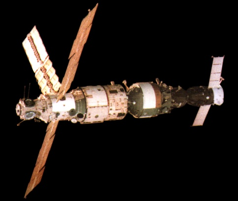 A view of Mir from Soyuz TM-2 showing the station in its early configuration. In view (from left to right) are the Base Block, Kvant-1 module and docked Soyuz TM-3 spacecraft.