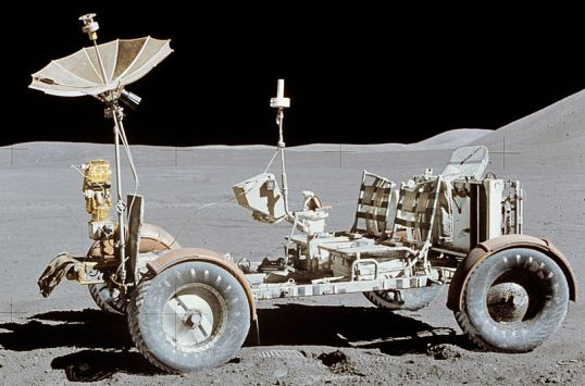 One of a series of images taken as a pan of the Apollo 15 landing site, taken by Commander Dave Scott. Featured is the Lunar Roving Vehicle at its final resting place after EVA-3. At the back is a rake used during the mission. Also note the red Bible atop the hand controller in the middle of the vehicle, placed there by Scott.