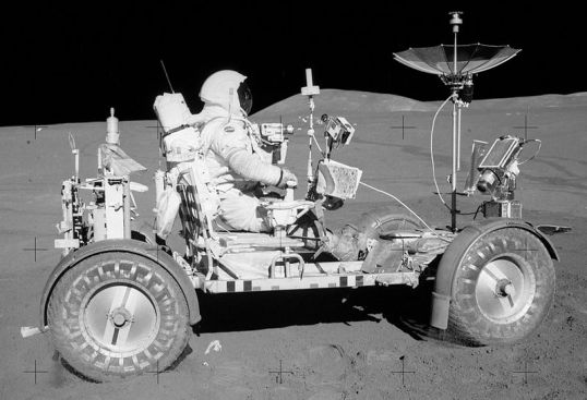 Image from Apollo 15, taken by Commander David Scott at the end of EVA-1. Lunar Module Pilot Jim Irwin is seen with the Lunar Roving Vehicle, with Mount Hadley in the background. Seen on the back of the Rover are two SCBs mounted on the gate, along with the rake, both pairs of tongs, the extension handle with scoop probably attached, and the penetrometer. Note that the TV camera is pointed down, in the stowed position.