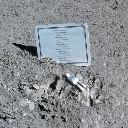 A close-up view of a commemorative plaque left on the Moon at the Hadley-Apennine landing site in memory of 14 NASA astronauts and USSR cosmonauts, now deceased. Their names are inscribed in alphabetical order on the plaque. The plaque was stuck in the lunar soil by Astronauts David R. Scott and James B. Irwin during their Apollo 15 lunar surface extravehicular activity. The tiny, man-like object represents the figure of a fallen astronaut/cosmonaut.