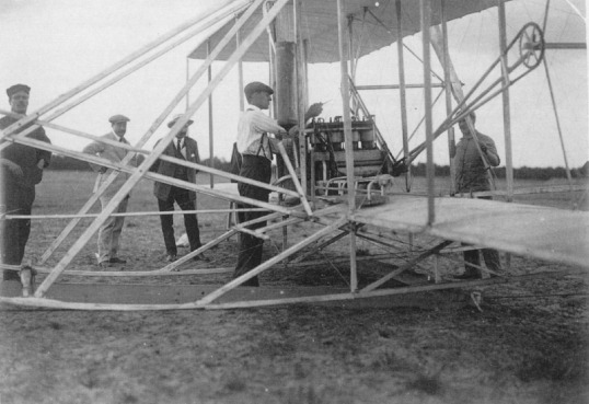 Wilbur adjusts the engine of his airplane at Le Mans, France. The aircraft was damaged in shipment and had to be rebuilt entirely