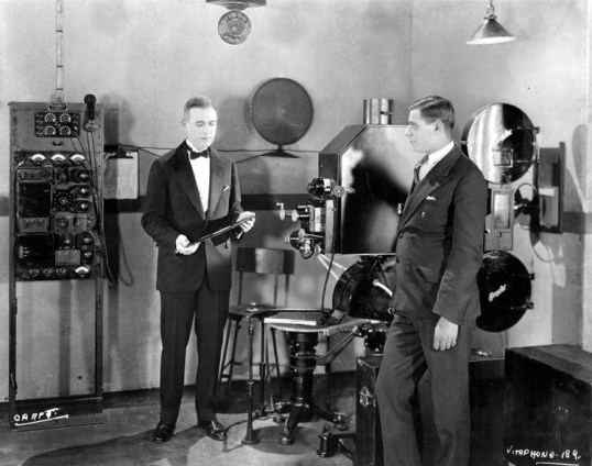 A Vitaphone projection setup at a 1926 demonstration. Western Electric Engineer E. B. Craft (on the left) is holding a soundtrack disc. The turntable, on a massive tripod base, is at lower center