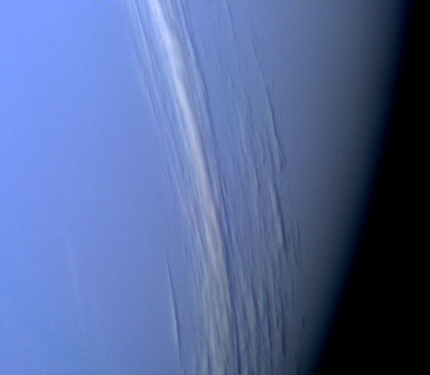 This Voyager 2 high resolution color image, taken 2 hours before closest approach, provides obvious evidence of vertical relief in Neptune's bright cloud streaks. These clouds were observed near Neptune's east terminator. The linear cloud forms are stretched approximately along lines of constant latitude and the Sun is toward the lower left. The bright sides of the clouds which face the Sun are brighter than the surrounding cloud deck because they are more directly exposed to the sun. Shadows can be seen on the side opposite the sun.