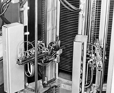 Shown here is a close-up of dual access arms used to record data on or read data from the IBM 350 disk memory unit in an IBM 305 RAMAC. The second access arm, available as an additional feature, made it possible for one access unit to be in a position for reading or writing while the other arm moved to the next storage record. As both arms could be in motion simultaneously, RAMAC processing time was substantially reduced. The disk unit for 305 systems could be obtained with storage capacities of five million digits and 10 million digits, and could be installed either singly or in pairs.