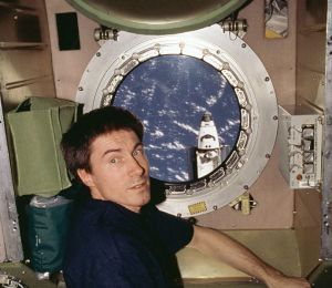 S. K. Krikalev in the Zvezda module. Atlantis is shown outside the window, flying mission STS-98.