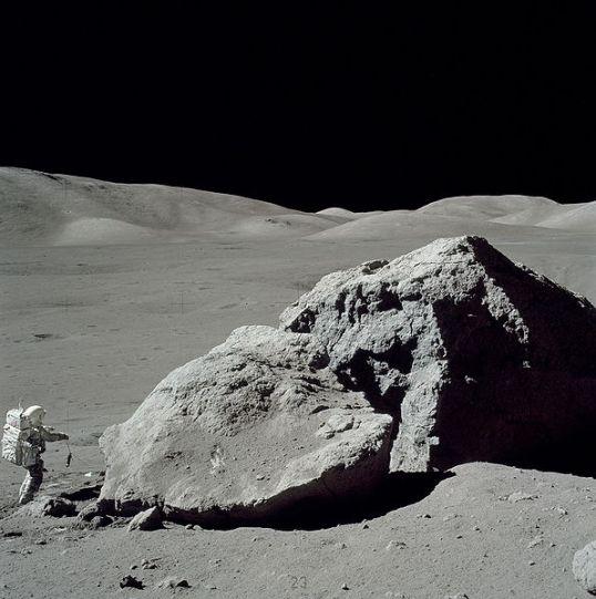 Scientist-Astronaut Harrison H. Schmitt is photographed standing next to a huge, split boulder