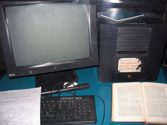 """This NeXT workstation (a NeXTcube) was used by Tim Berners-Lee as the first Web server on the World Wide Web. It is shown here as displayed in 2005 at Microcosm, the public science museum at CERN (where Berners-Lee was working in 1991 when he invented the Web). The document resting on the keyboard is a copy of """"Information Management: A Proposal,"""" which was Berners-Lee's original proposal for the World Wide Web. The partly peeled off label on the cube itself has the following text: """"This machine is a server. DO NOT POWER IT DOWN!!"""" Just below the keyboard (not shown) is a label which reads: """"At the end of the 80s, Tim Berners-Lee invented the World Wide Web using this Next computer as the first Web server."""" The book is probably """"Enquire Within upon Everything"""", which TBL describes on page one of his book Weaving the Web as """"a musty old book of Victorian advice I noticed as a child in my parents' house outside London"""". This is a new upload by Coolcaesar of the original JPEG file"""