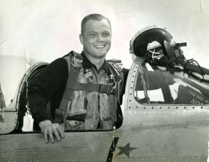 John Glenn poses in the cockpit of his